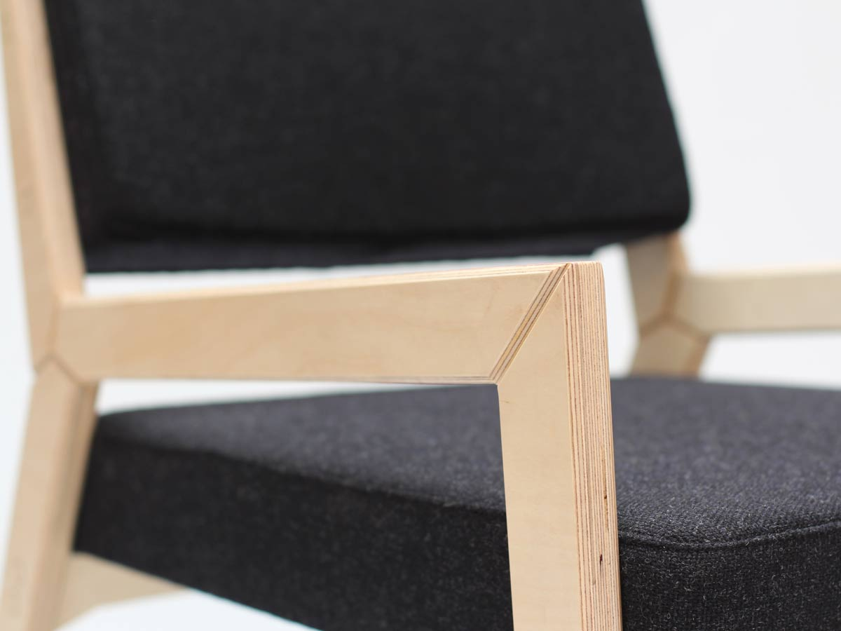 Liqui-Contracts-CNC cut birch ply upholstered arm chair showing the arm in detail with the charcoal grey tweed seat and back