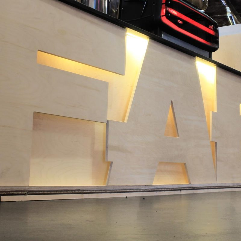 Detail of front of Faema trade stand with backlit CNC cut logo lettering in birch ply by Liqui Exhibitions for the London Coffee Festival