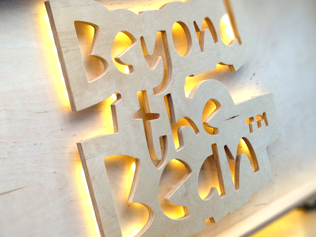 Liqui Exhibition Stand Design - Beyond The Bean trade stand counter showing cut-out logo in birch ply with back-lighting