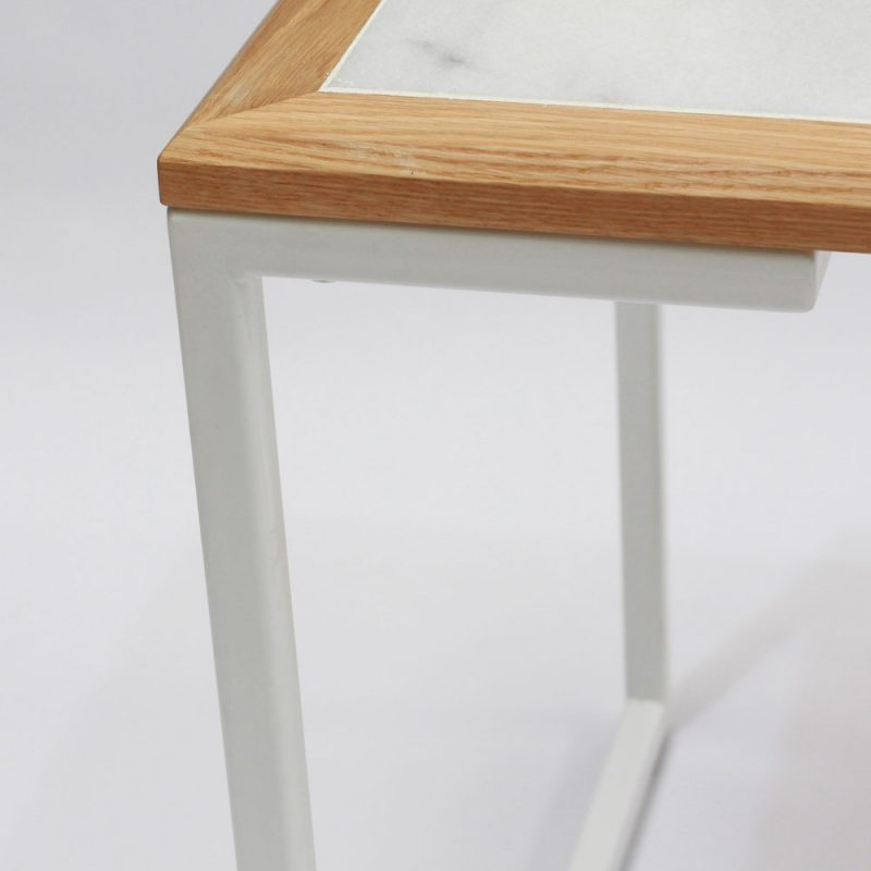 Studio Cafe Table by Liqui - corner detail. The white powder coated stainless steel frame has a marble top framed in sustainably sourced oak.