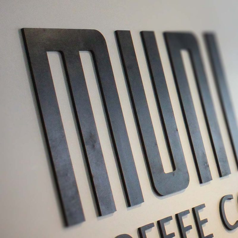 branding2- Muni Coffee sign design by Crate47 showing close-up of cut-out logo on restaurant wall