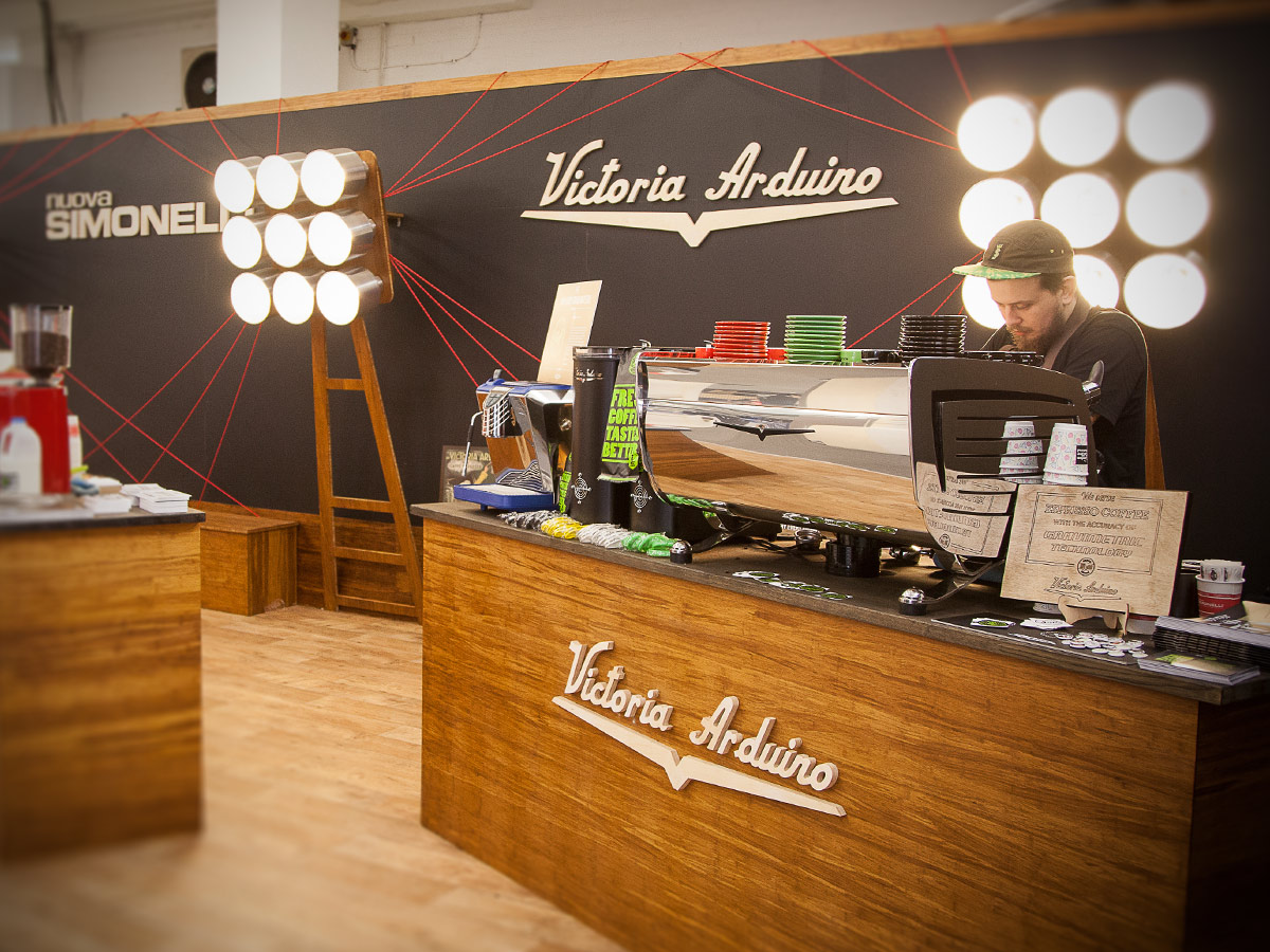 Liqui Exhibition Stand Design - NUOVA SIMONELLI & VICTORIA ARDUINO trade stand at London Coffee Festival showing bespoke floodlight style lighting installation