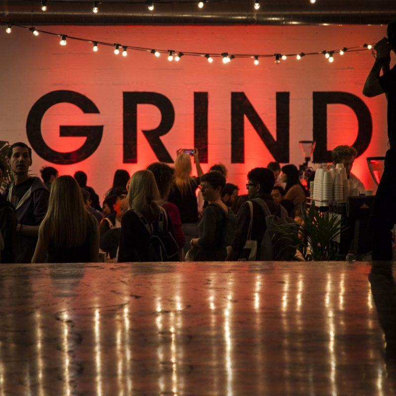 Liqui Brand Experience - Grind-2 - Party scene with people dancing and talking in a red glow with strings of overhead lights reflected on surface.