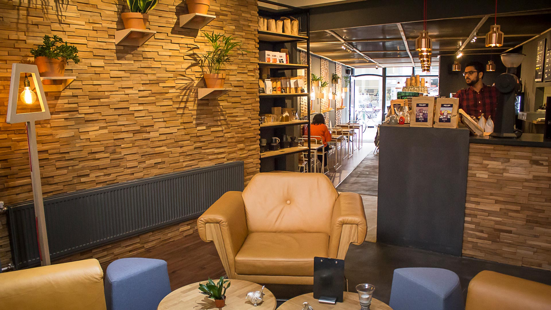 The Kaafi coffee shop in The Hague designed and installed by Liqui. Interior view showing Hove Club Chairs in leather with Darla Stools, a Symbol Light and Studio Coffee Table.